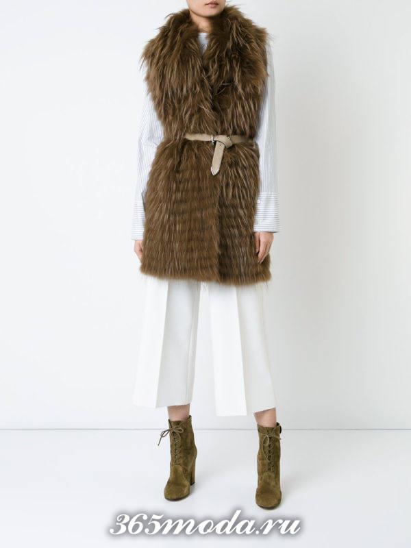 меховой жилет с поясом и белыми брюками