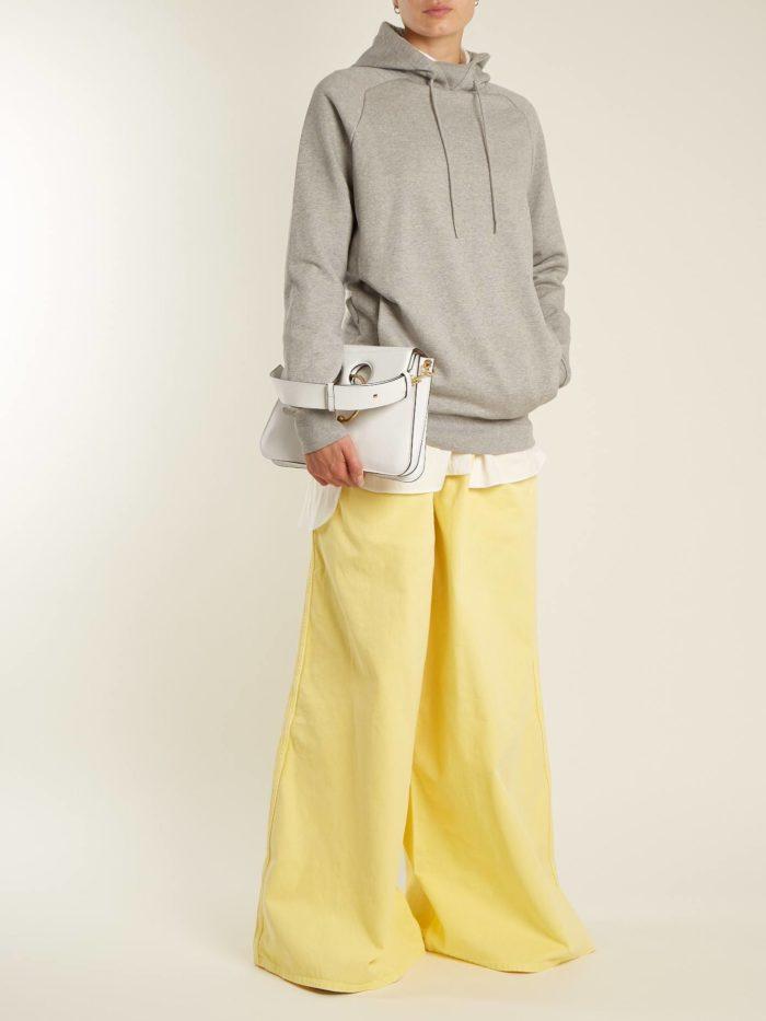 желтые брюки клеш и серая толстовка